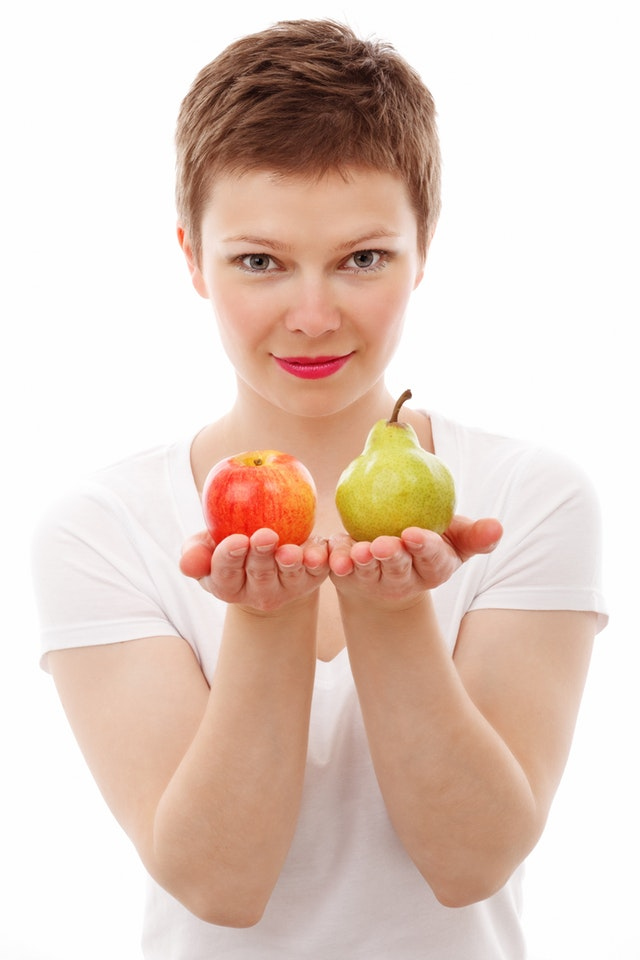 A slim woman holding up an apple and a pear.