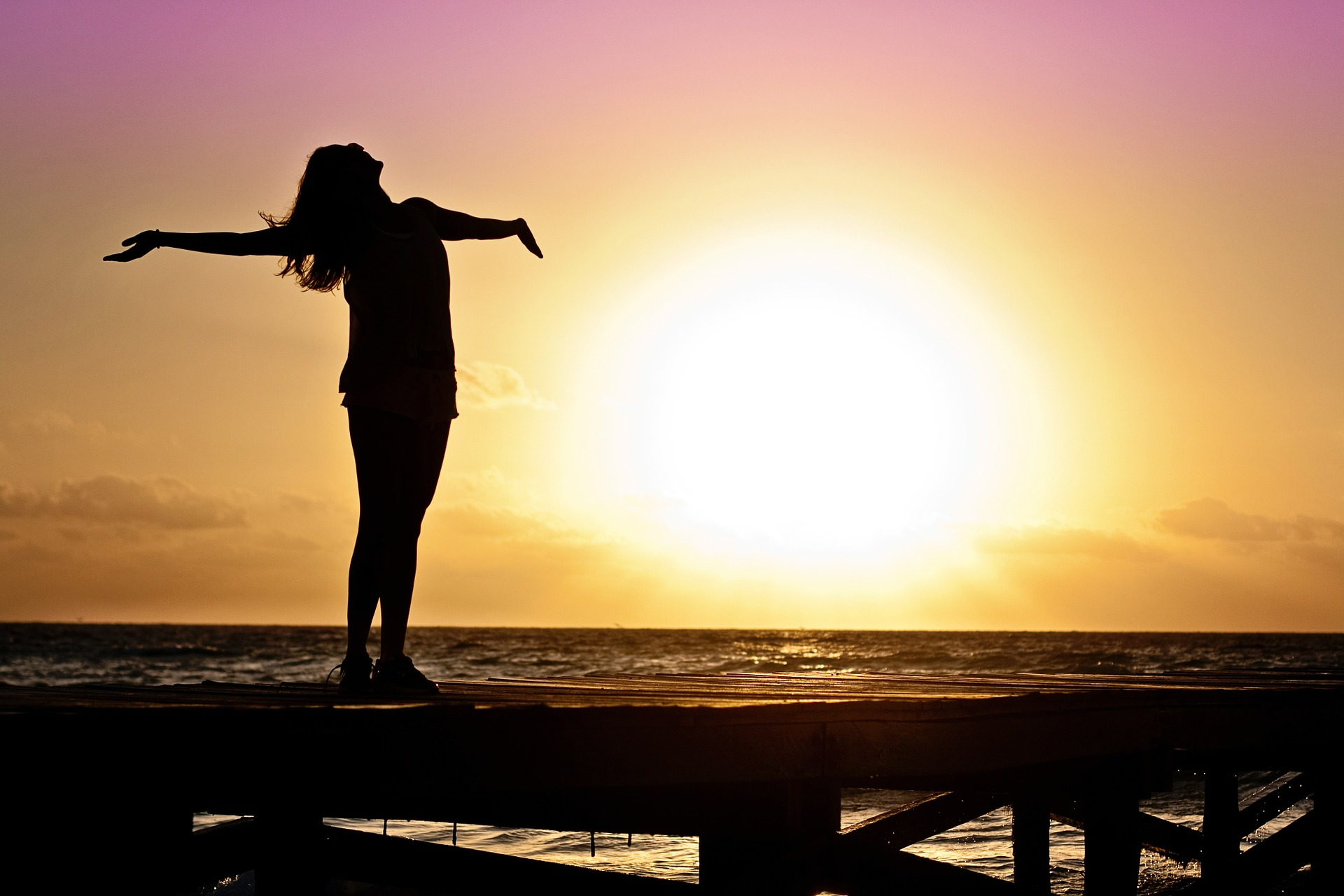 Woman standing on a dock, taking in vitamin D from sunlight.